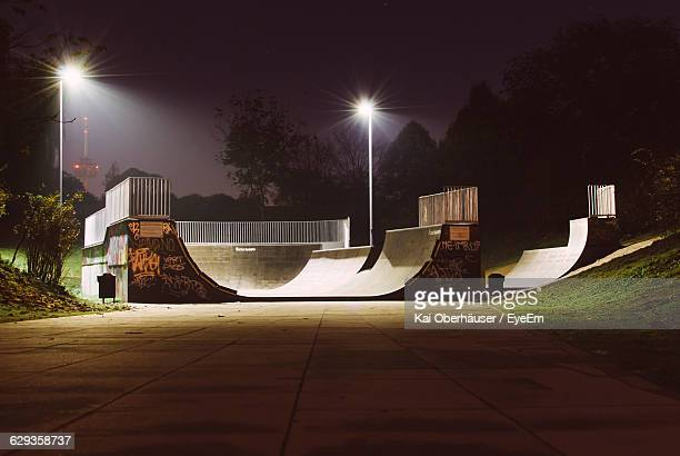 illuminated street lights at skateboard park during night - skateboard park stock pictures, royalty-free photos & images