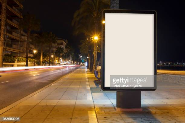 illuminated street lights on road in city at night - luce stradale foto e immagini stock