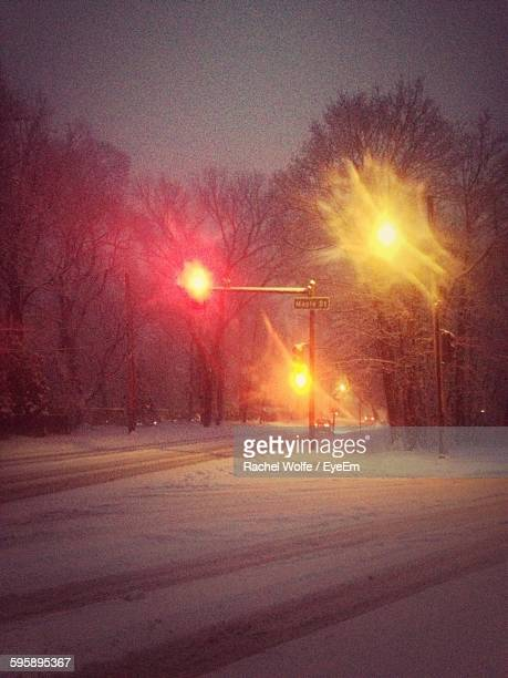 illuminated street lights on snow covered field at night - rachel wolfe stock pictures, royalty-free photos & images