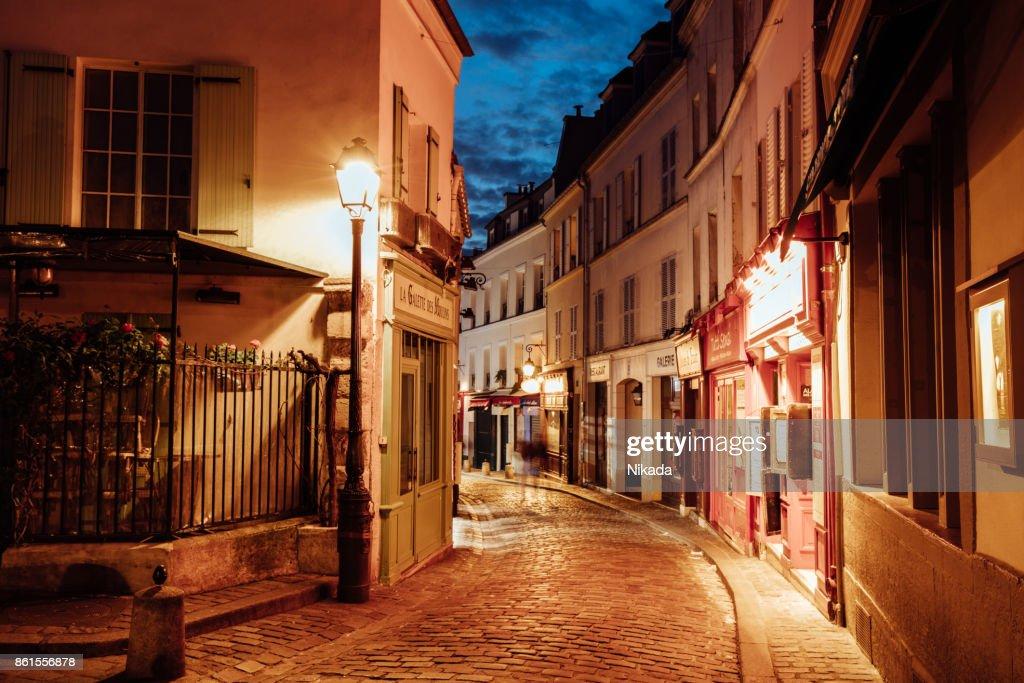 Illuminated streets of Monmartre quarter, street in Paris at night : Stock Photo