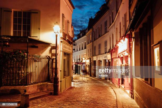 illuminated streets of monmartre quarter, street in paris at night - vintage restaurant stock pictures, royalty-free photos & images