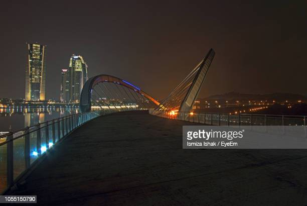 illuminated suspension bridge against sky at night - putrajaya stock photos and pictures