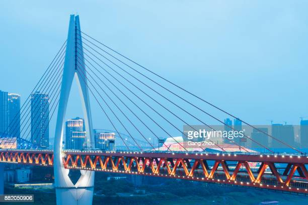 verlichte hangbrug over de rivier in de moderne stad - brug mens gemaakte bouwwerken stockfoto's en -beelden