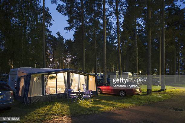 Illuminated tent by caravans in travel trailer park amidst trees at dusk