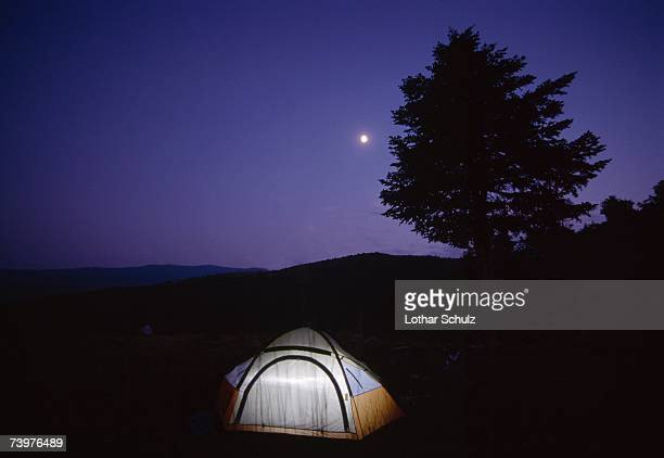 Illuminated tent in a field at night