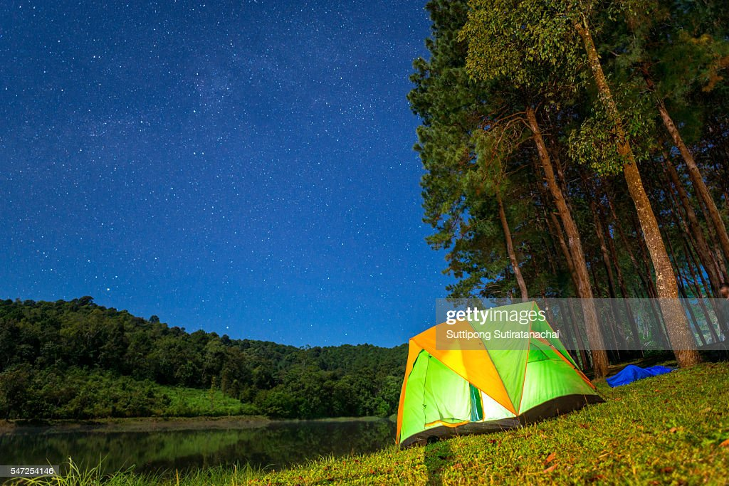 Illuminated tent in the winter forest camp by the lake at night : Stock Photo