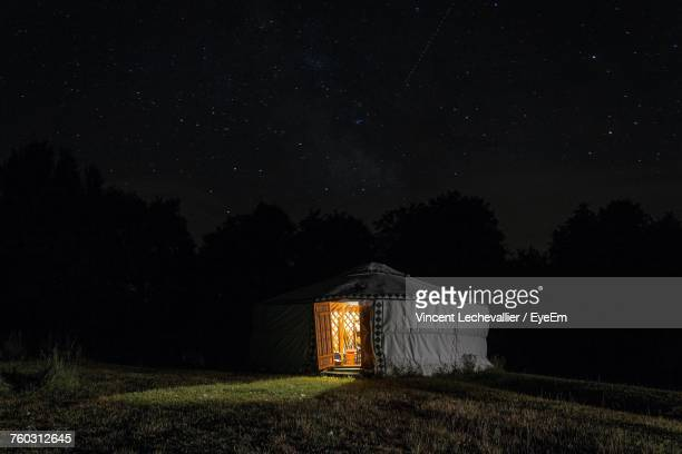 illuminated tent on field against sky at night - yurt stock pictures, royalty-free photos & images