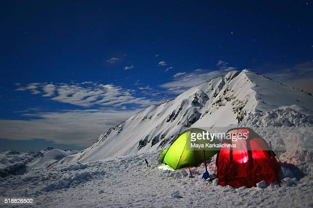 Illuminated tents in front of a peak
