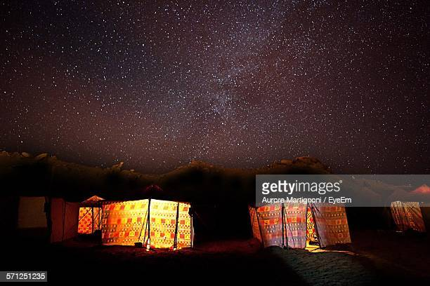 Illuminated Tents In Sahara Desert Against Constellations In Sky
