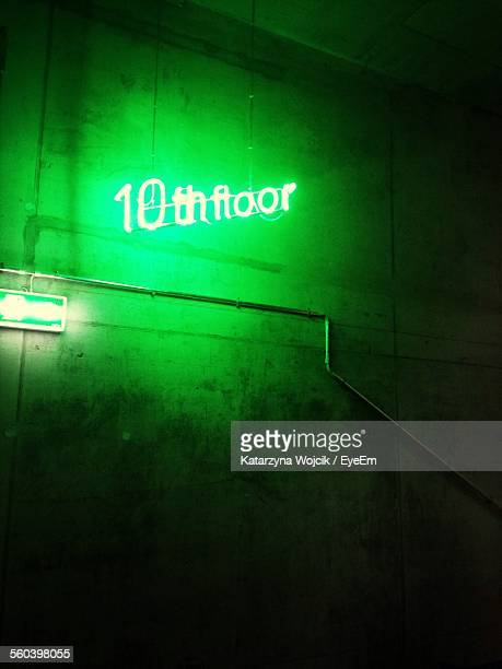 Illuminated Text Hanging Against Green Wall