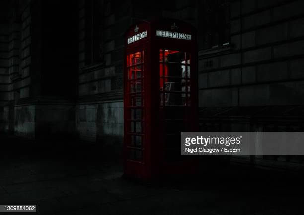 illuminated text on phone box by street in city at night - western script stock pictures, royalty-free photos & images