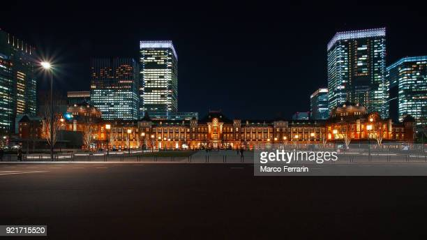 illuminated tokyo station in marunouchi commercial district at night, japan - tokyo station stock photos and pictures
