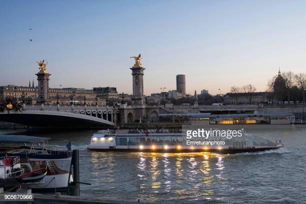 illuminated tour boat passing under the alexandre 3 bridge at sunset,paris. - emreturanphoto stock pictures, royalty-free photos & images