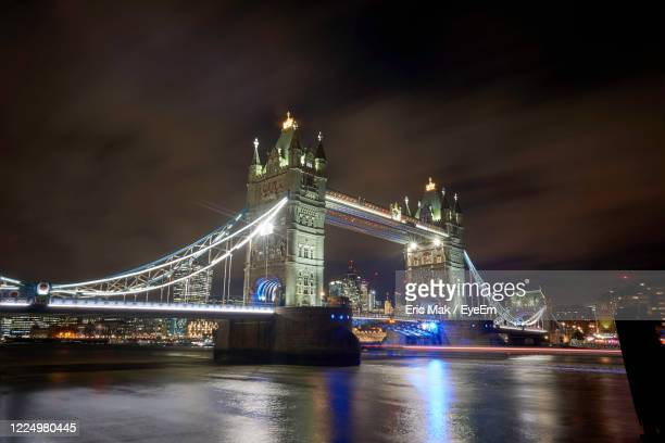 illuminated tower bridge over river at night - city gate stock pictures, royalty-free photos & images