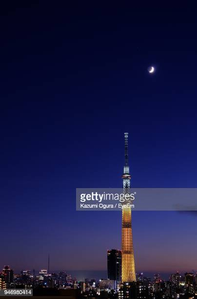 Illuminated Tower In City Against Clear Blue Sky At Night