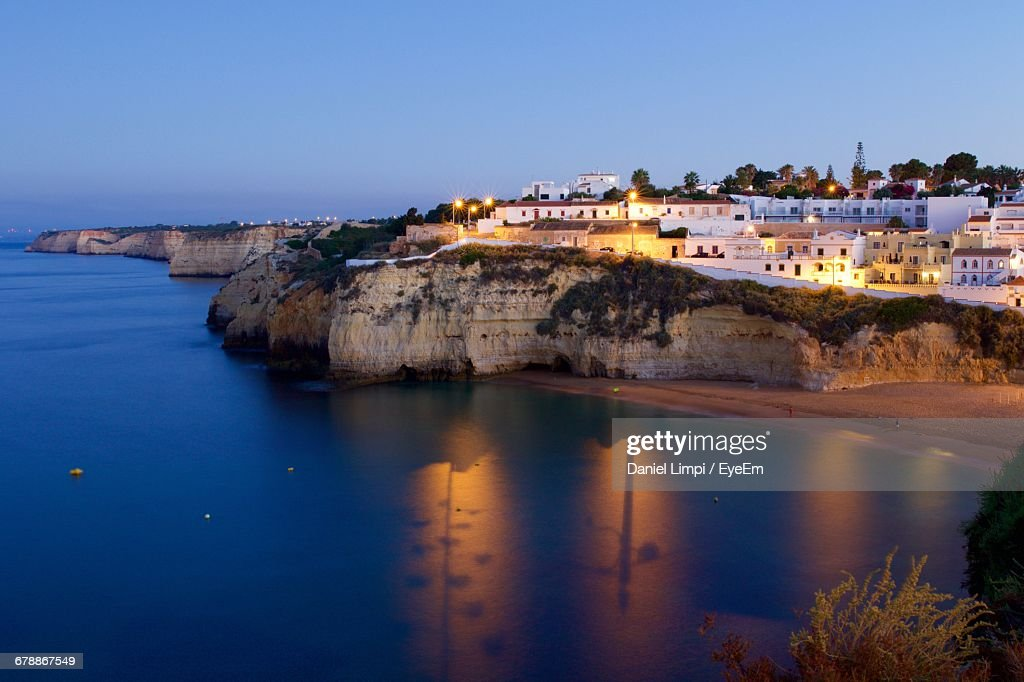 Illuminated Town By Sea Against Clear Sky At Dusk : Stock Photo