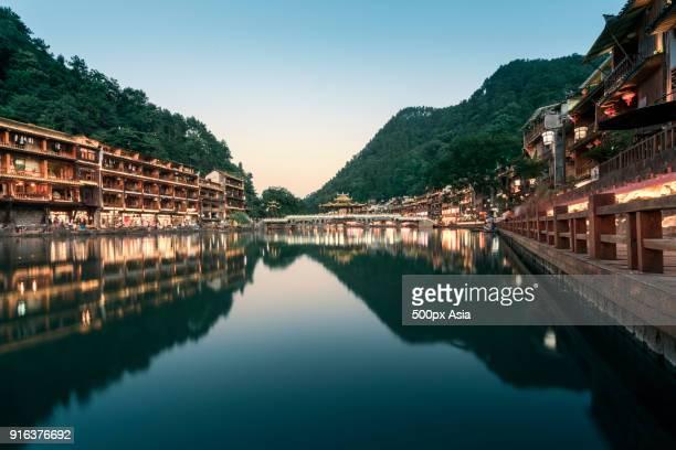 Illuminated traditional houses and bridge over Tuo Jiang River at dusk, Fenghuang, Hunan, China