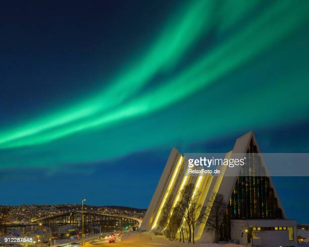 illuminated tromso cathedral at night with beautiful green shapes of aurora borealis - cathedral stock pictures, royalty-free photos & images