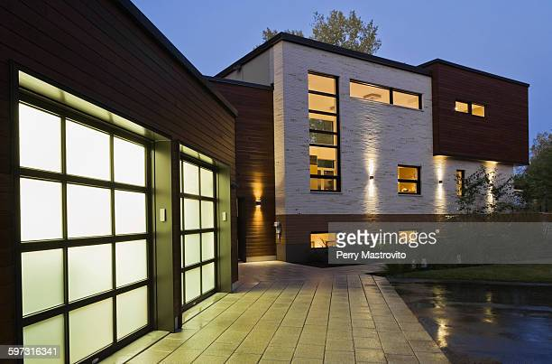 Illuminated two car garage of modern cubist style residential home at dusk, Quebec, Canada
