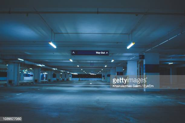 illuminated underground parking lot at night - parking garage stock pictures, royalty-free photos & images