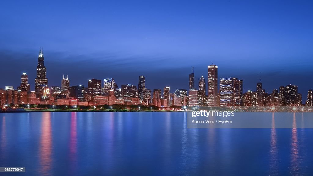 Illuminated Urban Skyline By Lake Michigan At Dusk