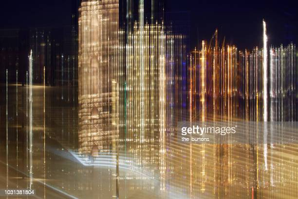 illuminated urban skyline with blurred lights - illuminate stock photos and pictures