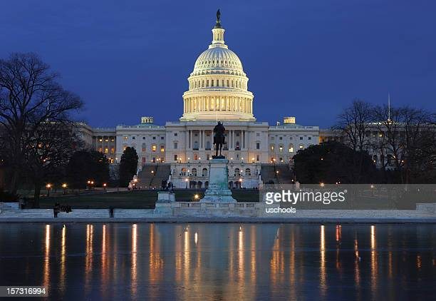 Illuminated US Capitol building with reflection on ice