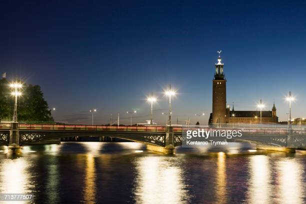 Illuminated Vasabron bridge over Lilla Vartan with Stockholm City Hall against sky at night