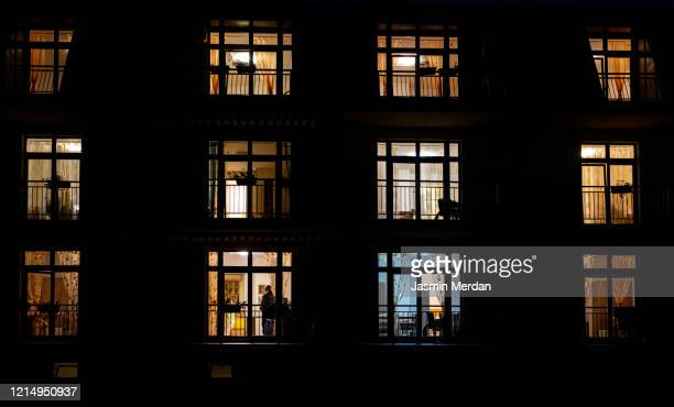 illuminated windows of night house with people inside - ロックダウン ストックフォトと画像
