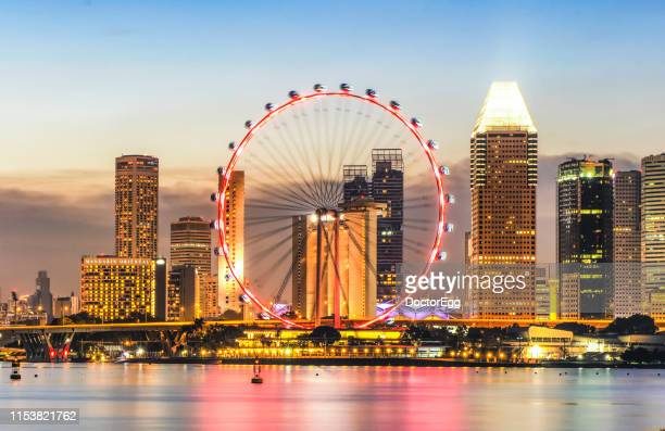 illumination of singapore fly giant ferris wheel with skyscraper buildings background at marina bay, singapore - singapore flyer stock photos and pictures