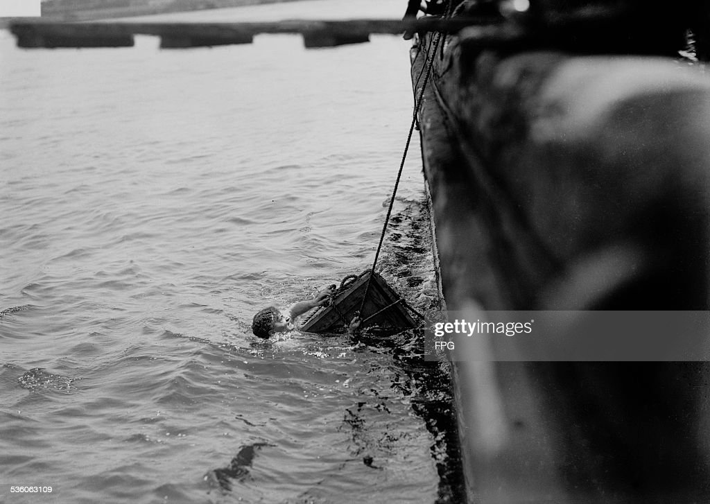 Illusionist and escape artist Harry Houdini is submerged in the East River in a crate, New York City, 7th July 1912. He escaped in just under a minute.