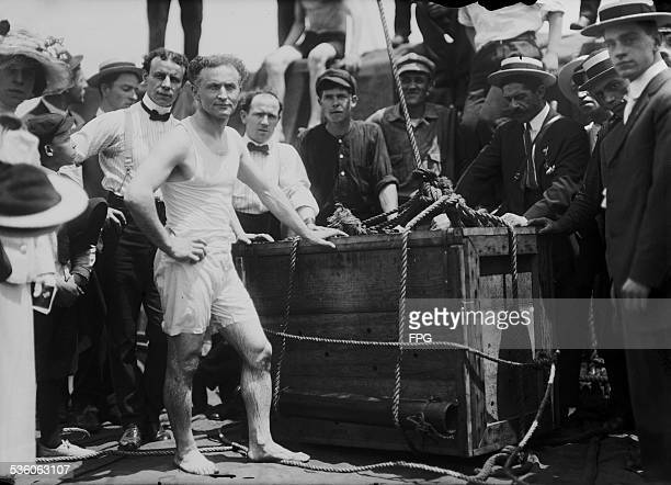 Illusionist and escape artist Harry Houdini performs his famous stunt whereby he was submerged in the East River in a crate New York City 7th July...
