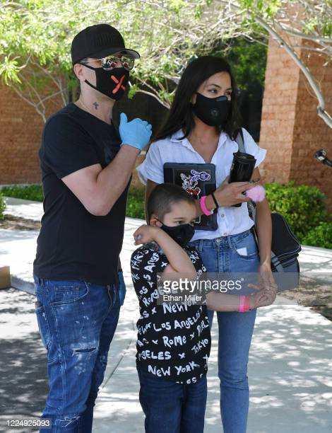 Illusionist Criss Angel, his son Johnny Crisstopher Sarantakos and Shaunyl Benson visit as Angel helps to give out food and other items at the Cure 4...