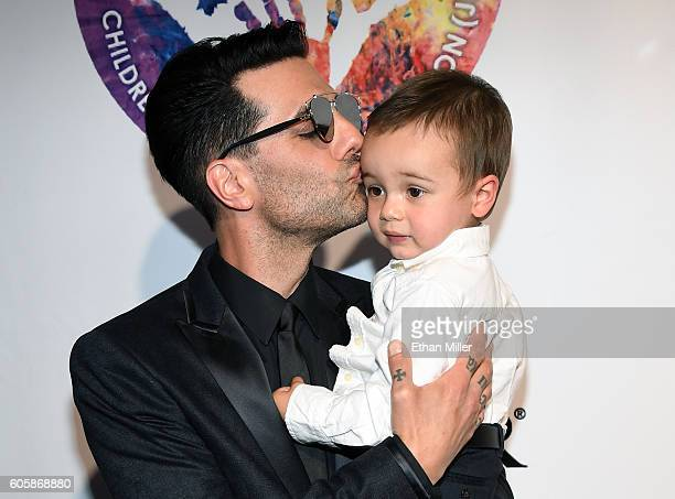 Illusionist Criss Angel kisses his son Johnny Crisstopher Sarantakos at Criss Angel's HELP charity event at the Luxor Hotel and Casino benefiting...