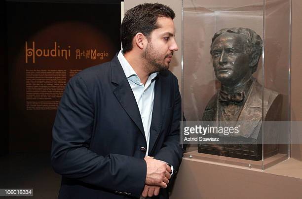 illusionist David Blaine poses next to a statue of Harry Houdini during the 'Houdini Art And Magic' exhibition press preview at The Jewish Museum on...