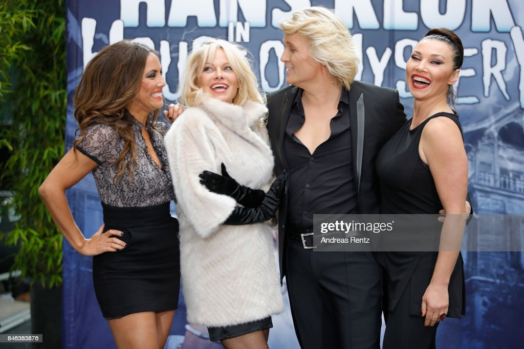 Illusionist Hans Klok and Pamela Anderson and their assistants attend a photocall for their upcoming show 'House of Mystery' on September 13, 2017 in Cologne, Germany.