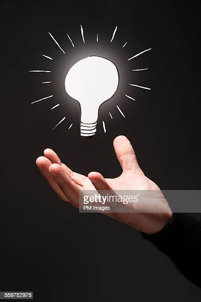 Illustrated light bulb over hand