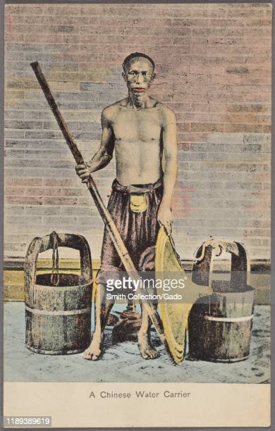 Illustrated postcard of a Chinese water carrier, standing by water pails holding a yoke and a straw hat, published by M. Sternberg, 1912. From the...