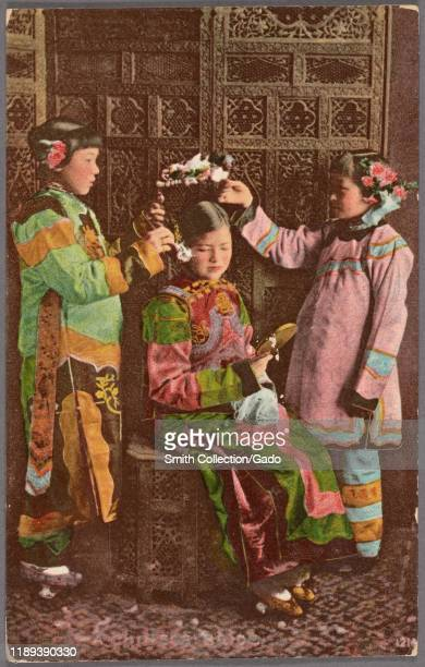 Illustrated postcard of a group of Chinese girls dressed in traditional attire two putting a flower wreath on the head of the third one published by...