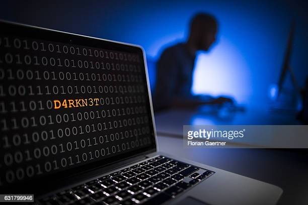 Illustration about 'Darknet' Closeup of a laptop with binary code In the background a man sits on a computer on January 13 2017 in Berlin Germany