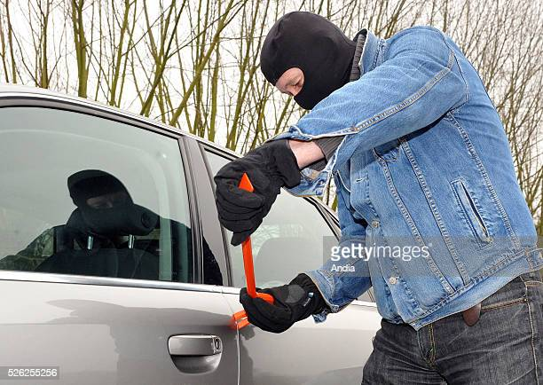 illustration burglary and car theft Man wearing a balaclava holding a wrecking bar about to break open the side door of a vehicle