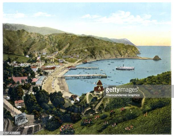 Illustration, from a souvenir album of Southern California scenes, shows a view looking down on the town of Avalon and its beach, on South Catalina...