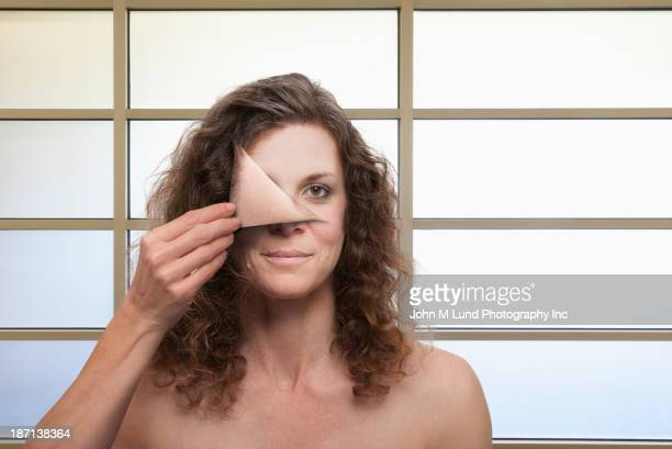 Illustration of woman peeling mask off