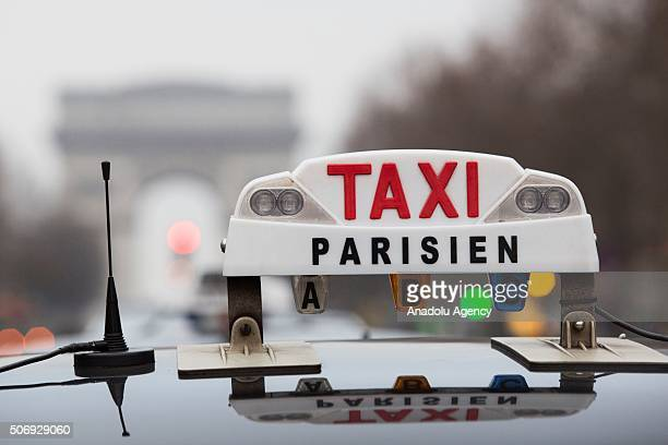 Illustration picture shows a Parisian taxi in front of Arc de Triomphe in Paris France on January 26 2016 French taxi drivers are protesting against...