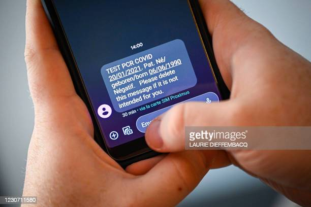 Illustration picture shows a person receiving an sms announcing a negative result of a Covid-19 test, Thursday 21 January 2021 in Brussels. BELGA...