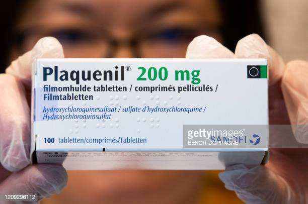 Illustration picture shows a pharmacist holding a box of Plaquenil Monday 06 April 2020 Belgium goes into its fourth week of confinement in the...