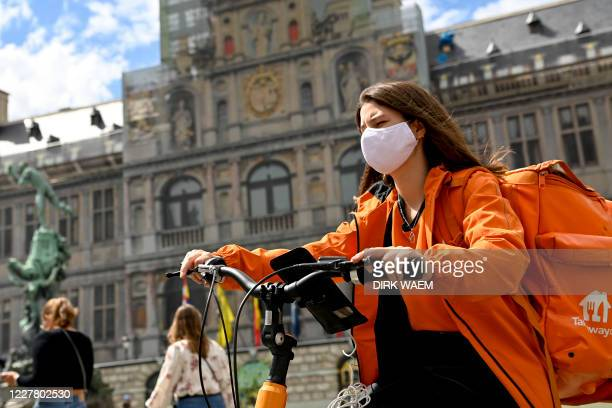 Illustration picture shows a woman working for Take Away, rides a bike with a mask in the city center of Antwerp, Monday 27 July 2020. The Covid-19...
