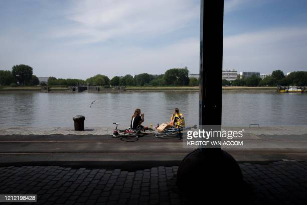 Illustration picture shows people sitting along the Scheldt river , in the city center of Antwerp, Friday 08 May 2020, where stores are preparing for...