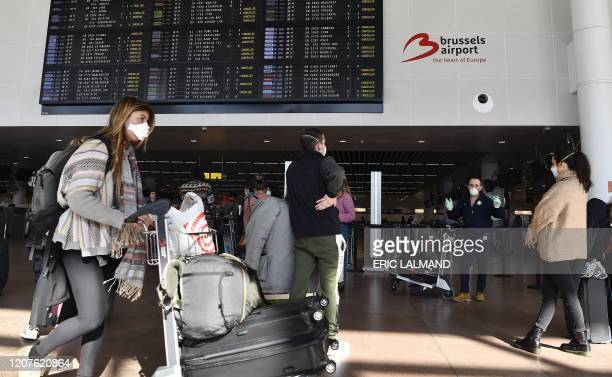 Illustration picture shows people wearing mouth masks pass by the departures information panels, at Brussels Airport, in Zaventem, Wednesday 18 March...