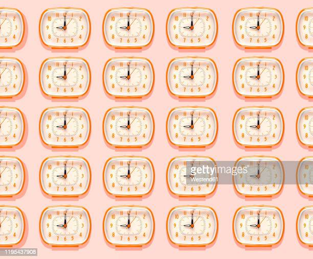 3d illustration, row of orange alarm clocks at nine o'clock pattern on pink background - repetition stock pictures, royalty-free photos & images